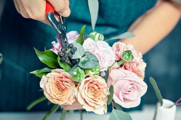 Sluit omhoog mening over vrouwelijke bloemist die vers bloemboeket in winkel maken. vrouw gesneden bos voor het maken van decoraties en arrangementen. kopieer ruimte. professioneel bloemistconcept