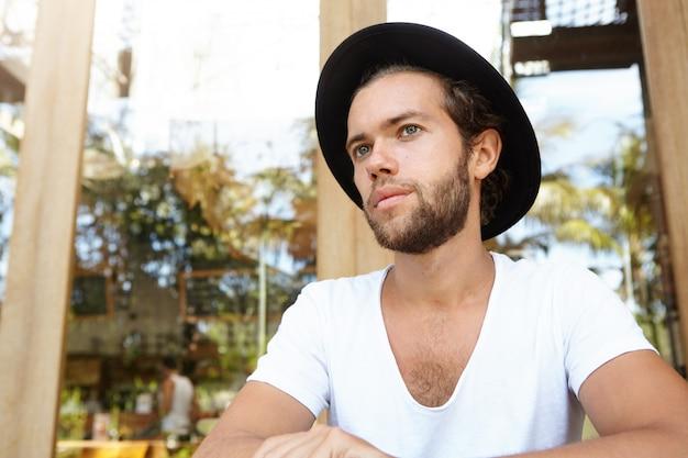 Sluit omhoog mening van aantrekkelijke modieuze jonge gebaarde mens in v-halsoverhemd en zwarte hoedenzitting bij stoepkoffiewinkel