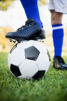 Sluit omhoog mening van ballon onder voetbalschoenen