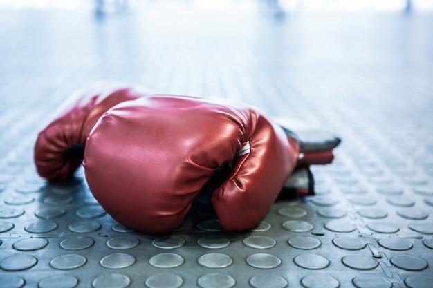Sluit omhoog mening van bokshandschoenen op industriële vloer