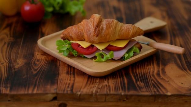 Sluit omhoog mening van croissantsandwich met ham en kaas op houten dienblad