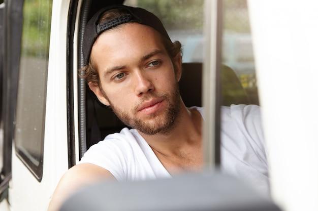 Sluit omhoog mening van de aantrekkelijke jonge gebaarde mens in snapback zitting binnen cabine van zijn witte jeep
