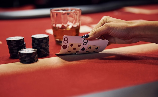 Sluit omhoog mening van de handen van de vrouw. meisje speelt pokerspel per tafel in casino en controleert kaarten