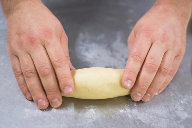Sluit omhoog mening van de handen van een bakkersman die een deeg rolt.
