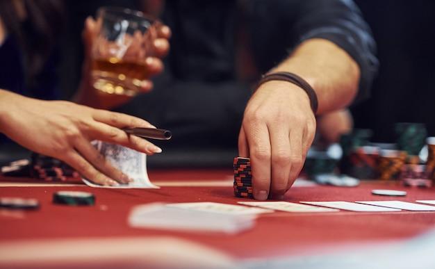 Sluit omhoog mening van de handen van elegante jongeren die het spelen van poker in casino
