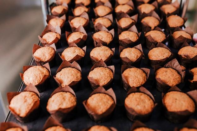 Sluit omhoog mening van de holdingsrek van de vrouwenholding van croissants in een bakkerij.