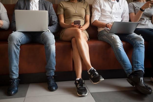 Sluit omhoog mening van diverse mensen die gebruikend elektronische apparaten zitten