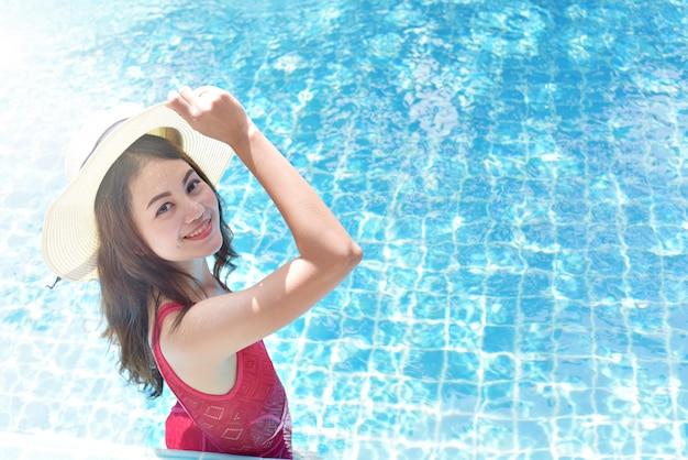 Sluit omhoog mening van een aantrekkelijke jonge vrouw die op het zwembad van een spa ontspant. reizen, geluk emotie, zomervakantie concept.