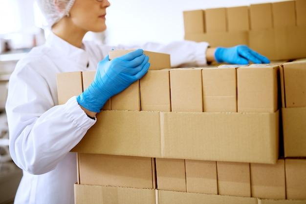 Sluit omhoog mening van een jonge geconcentreerde vrouwelijke werknemer in steriele doeken en blauwe rubberhandschoenen die gestapelde dozen in een fabrieksopslagruimte tellen.