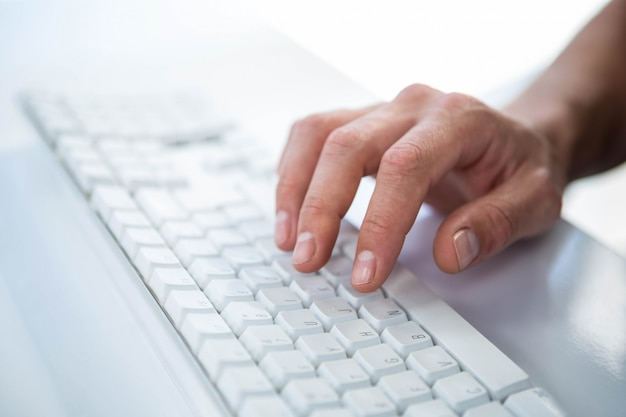 Sluit omhoog mening van een mannelijke hand die op toetsenbord typen