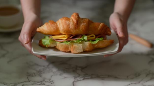 Sluit omhoog mening van een meisje dat ontbijt heeft, houdend een plaat van croissantsandwich
