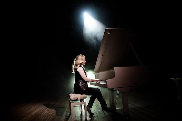 Sluit omhoog mening van een meisje speelt piano in de concertzaal bij scène