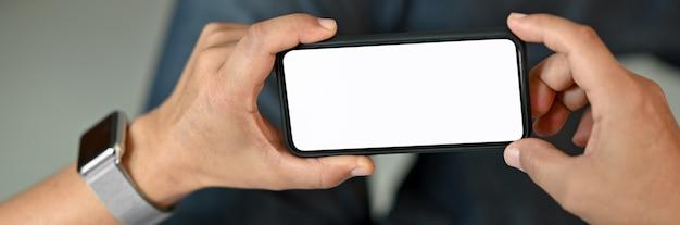Sluit omhoog mening van een mens gebruikend horizontale lege het schermsmartphone