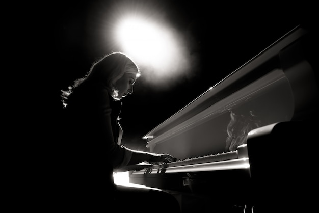 Sluit omhoog mening van een piano van meisjesspelen in de concertzaal bij de scène