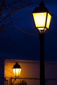 Sluit omhoog mening van een traditionele europese straatlantaarnpool die bij nacht wordt aangestoken.