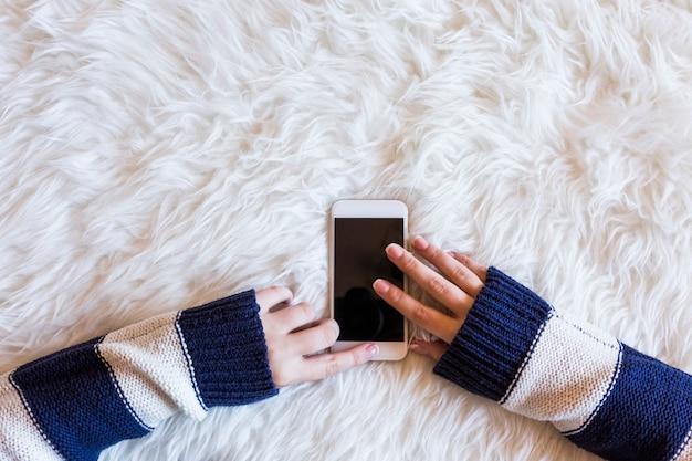 Sluit omhoog mening van een vrouw hans typend op haar mobiele telefoon, witte achtergrond. lifestyles. bovenaanzicht. millennial.