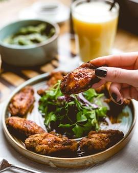 Sluit omhoog mening van een vrouwelijke hand die gebraden kippenvleugel houden