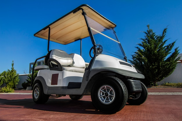 Sluit omhoog mening van een witte golfkar die op de weg wordt geparkeerd.
