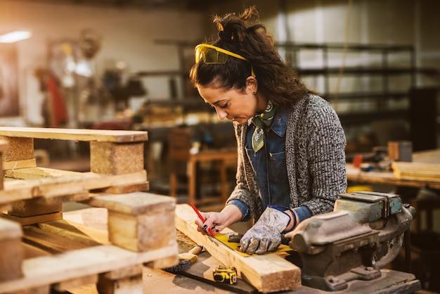 Sluit omhoog mening van hardwerkende geconcentreerde professionele ernstige de holdingsheerser en potlood van de timmermansvrouw terwijl het maken van tekens op het hout bij de lijst in de stoffenworkshop.