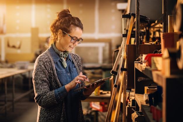Sluit omhoog mening van hardwerkende geconcentreerde professionele gemotiveerde bedrijfsvrouw die een tablet naast de plank met hulpmiddelen in de stoffenworkshop houden.