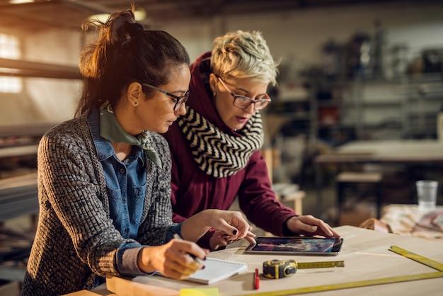 Sluit omhoog mening van hardwerkende geconcentreerde professionele gemotiveerde ingenieursvrouw die met een klant werken terwijl het kiezen van een product op een tablet in de zonnige stoffenworkshop.