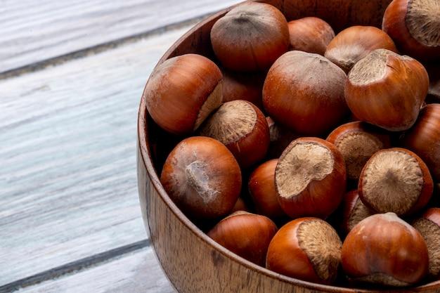 Sluit omhoog mening van hazelnoten in een kom op houten plattelander