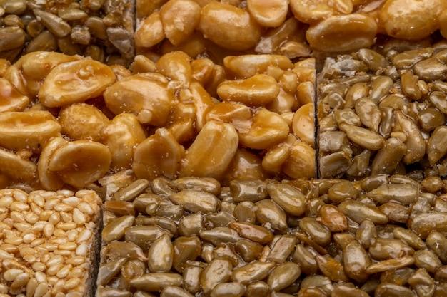 Sluit omhoog mening van honingsbars met pindasesam en zonnebloemzaden