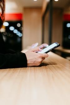Sluit omhoog mening van jonge vrouw binnen gebruikend mobiele telefoon in een koffie of een restaurant. onherkenbare persoon levensstijlen