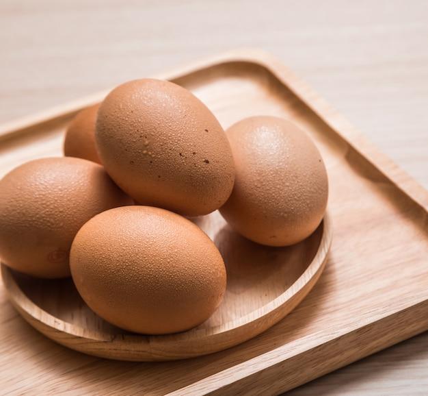 Sluit omhoog mening van kippeneieren op houten lijst