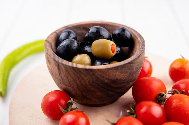 Sluit omhoog mening van kom van olijf en tomaten op scherpe raad