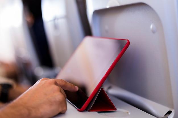 Sluit omhoog mening van mannelijke handen gebruikend een tablet in een vliegtuig. reizen concept