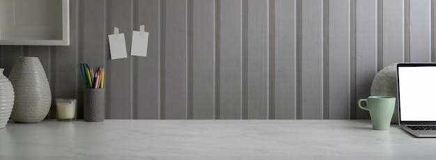 Sluit omhoog mening van modern huisbureau met laptop, kantoorbehoeftendecoratie en exemplaarruimte