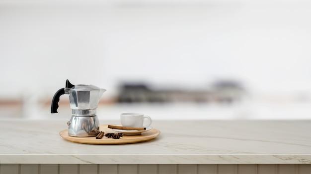 Sluit omhoog mening van onechte pot en koffiekop op marmeren bureau met vage keuken