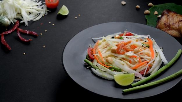 Sluit omhoog mening van papajasalade op zwarte plaat, kippengrill op groene taro en ingrediënten