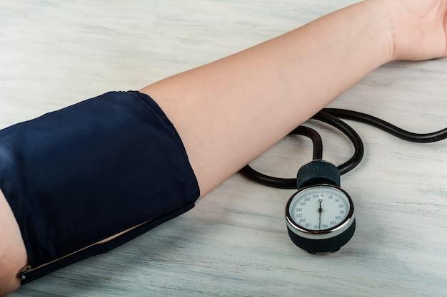 Sluit omhoog mening van persoon die zijn bloeddruk meet