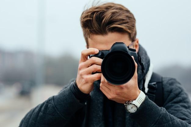 Sluit omhoog mening van professionele fotograaf die in openlucht foto's nemen.