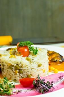Sluit omhoog mening van rijst met erwt en graan dat met kersentomaat wordt bedekt