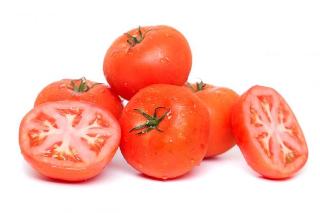 Sluit omhoog mening van rode die tomaten met waterdruppeltjes, op een witte achtergrond worden geïsoleerd.