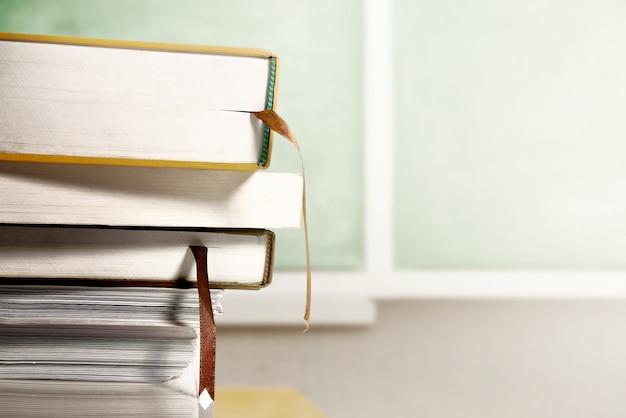 Sluit omhoog mening van stapel van boeken op houten lijst met bordachtergrond