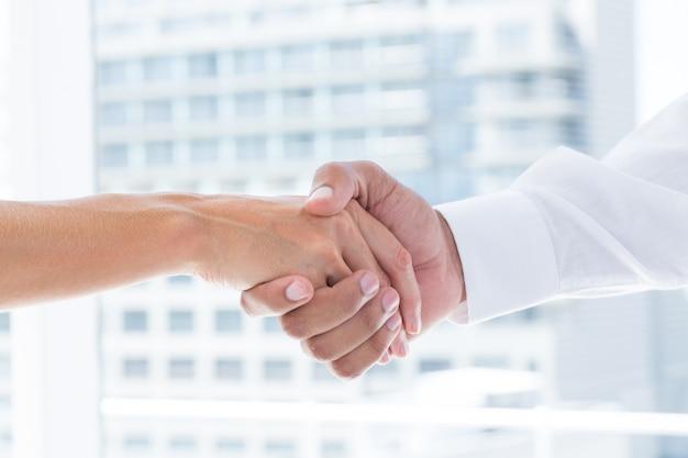 Sluit omhoog mening van twee bedrijfsmensen die handen schudden