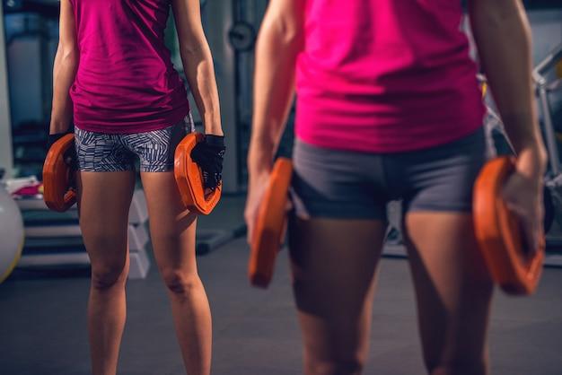 Sluit omhoog mening van twee jonge benen van de fitness sportieve actieve slanke vrouw terwijl het doen van oefeningen en het verwarmen met gewichten in de gymnastiek.
