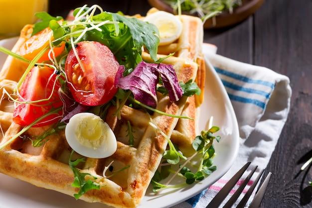 Sluit omhoog mening van vers gekookt gezond ontbijt met eigengemaakte wafels, tomaten en gesneden ei op een plaat