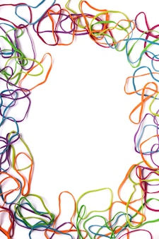 Sluit omhoog mening van verscheidene kleurrijke bureauelastiekjes die een rechthoek vormen die op een witte achtergrond wordt geïsoleerd.