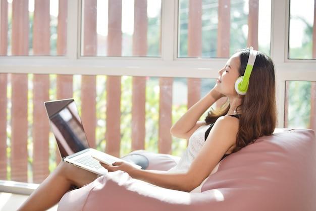 Sluit omhoog mening van vrouw die van tijd thuis geniet. mooie jonge glimlachende vrouw die aan laptop, slimme telefoon en slijtagehoofdtelefoons werkt terwijl thuis het zitten als grote comfortabele voorzitter.