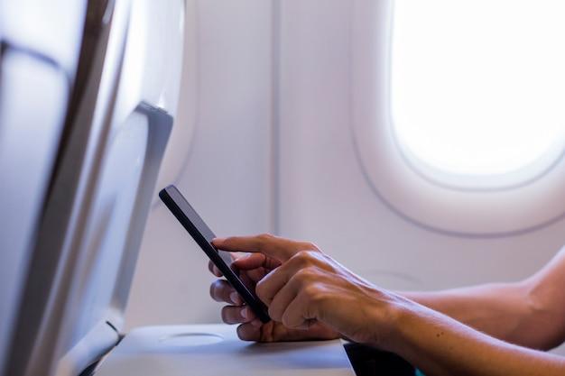 Sluit omhoog mening van vrouwelijke handen gebruikend een mobiele telefoon in een vliegtuig. reizen concept