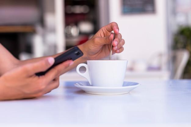 Sluit omhoog mening van vrouwenhanden houdend een kop van koffie en mobiele telefoon in een terras. ochtend, overdag en technologie