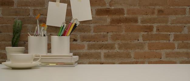 Sluit omhoog mening van werkruimte met briefpapier, verfhulpmiddelen, koffiekop, decoratie en exemplaarruimte op wit bureau
