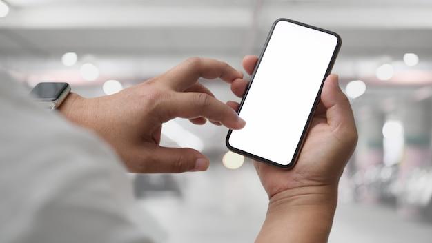 Sluit omhoog mening van zakenman gebruikend het lege schermsmartphone in autoparkeren