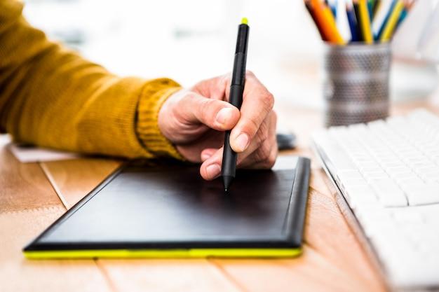 Sluit omhoog mening van zakenman gebruikend tablet grafisch in zijn bureau