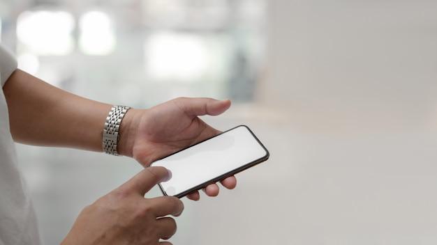 Sluit omhoog mening van zakenman het texting op lege het schermsmartphone in het bureau van glasverdelingen
